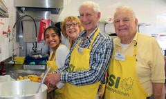 Volunteers stand in a kitchen smiling at the camera.
