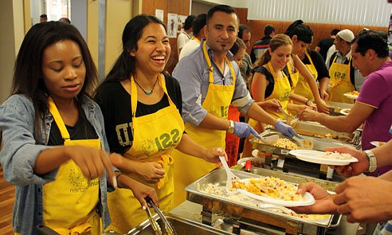 Volunteers at an SSI Community Kitchen are serving food, dressed in yellow approns.
