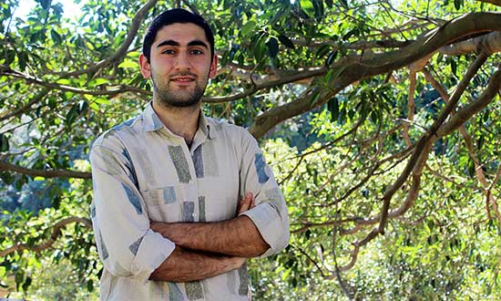 Former refugee Simon Shahin standing in front of a tree.