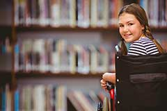 Girl in a wheelchair looking over her shoulder and smiling at the camera