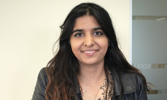 A headshot of Harpreet smiling at the camera against an office backdrop.