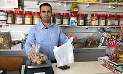 man at the counter of his grocery shop selling groceries
