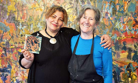 Two women in front of a large painting at an Art therapy class