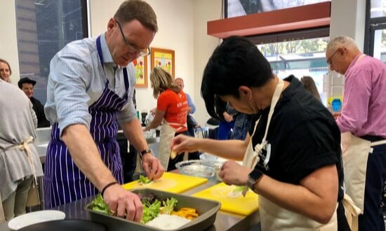 Participants cooking in the Disaster Chef Cook-Off at The Staples Bag Camperdown Grand Opening