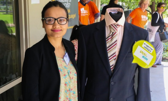 A woman standing with a mannequin in a suit
