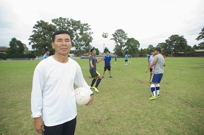 Soccer coach Essa Khan on a soccer field holding a ball.