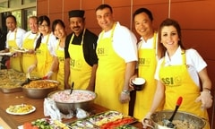 Volunteers in yellow SSI aprons serve food.