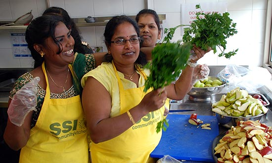 three women volunteers preparing a meal