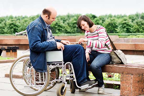 A photo of a man in a wheelchair being cared for by a woman.