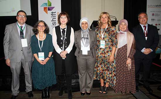 Seven people standing and smiling at the camera at the Cultural Shift Conference