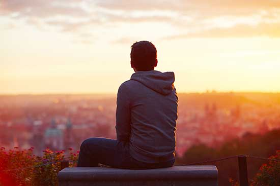 Young man sitting facing back and looking at the sunset