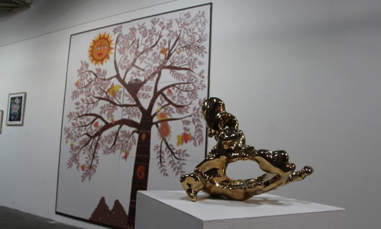 A sculpture and a mural are displayed in a gallery.