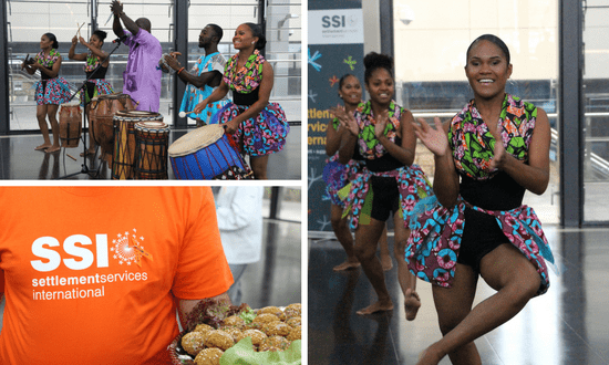 African dancers and drummers perform in traditional costumes. An SSI representatives hands out food.