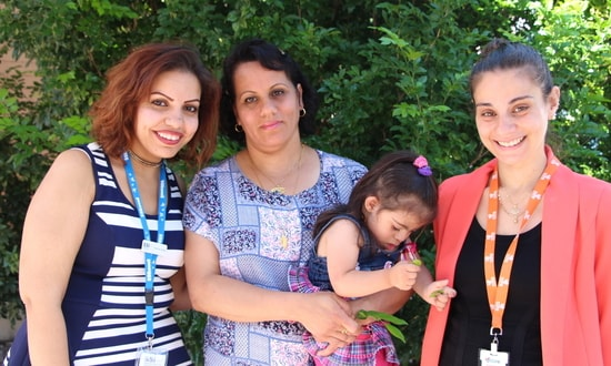 Basima holds her daughter and stands beside her case manager and the organiser of a women's group she attends.