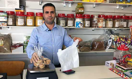 man at the counter of his new business, selling groceries