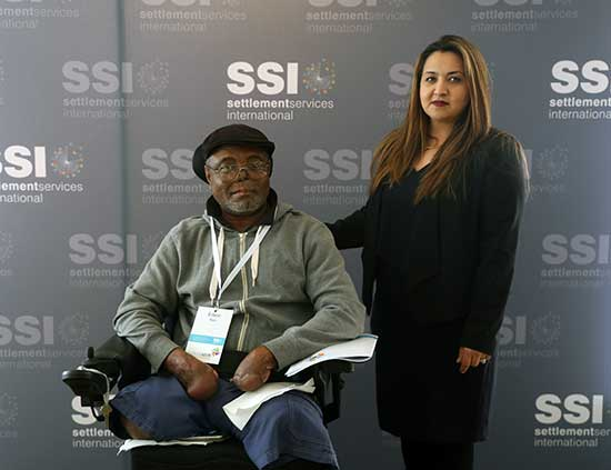 A man in a wheelchair and a woman standing next to him pose for the camera