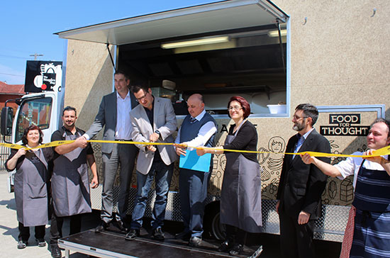 A man cuts a ribbon to symbolise the launch a food truck