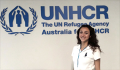 Talar Hagob standing in front of UNHCR banner