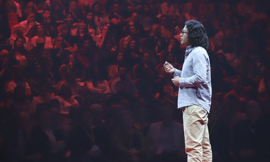 A man standing on stage giving a TEDx talk.