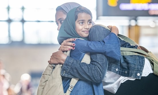 Refugee mother and daughter hug