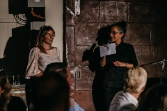 Two women giving a speech at a fundraising dinner.