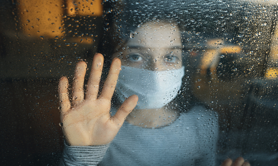 A girl wearing a mask and looking out from a window.