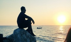 man sitting by sea at sunrise