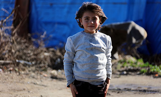 Young refugee in a camp smiles and looks happy