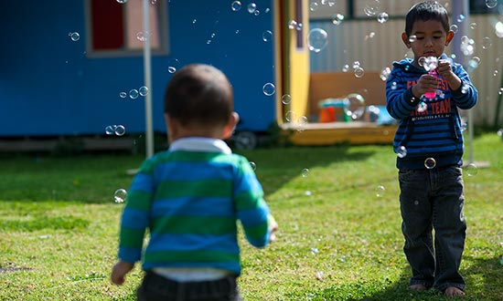 Two children playing together in a yard making bubbles.