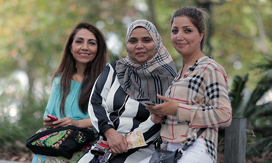 Three women from different cultural backgrounds smiling at camera.