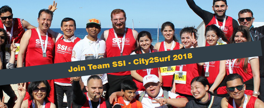 SSI's City2Surf Team celebrating after the race in 2016. They're dressed in red team singlets and are jumping in the air.
